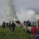 A group of migrant men run away from tear gas used by Macedonian police after migrants broke a fence at the northern Greek border point of Idomeni, Greece, Sunday, April 10, 2016. Thousands of migrants protested at the border and clashed with Macedonian police. (AP Photo/Amel Emric)