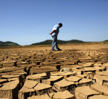A worker of SABESP, a Brazilian enterprise of Sao Paulo state, that provides water and sewage services to residential, commercial and industrial areas looks at the cracked ground of Jaguary dam in Braganca Paulista, 100 km from Sao Paulo January 31, 2014. This has been the hottest January on record in parts of Brazil, and the heat plus a severe drought has fanned fears of water shortages, crop damage, and higher electricity bills that could drag down the economy during an election year for President Dilma Rousseff.  REUTERS/Nacho Doce (BRAZIL - Tags: ENVIRONMENT ENERGY POLITICS TPX IMAGES OF THE DAY) - RTX182N6