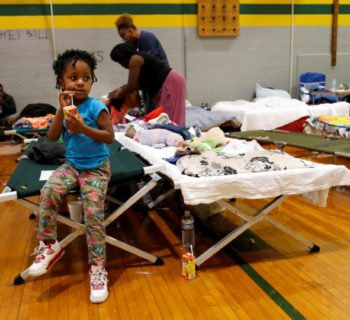 Nazareth Gray (4) sits on the edge of a cot at the Carver Heights Elementary School shelter after her and her grandmother Margaret (not pictured) were displaced by the effects of Hurricane Matthew in Goldsboro, North Carolina, U.S. October 12, 2016. REUTERS/Randall Hill