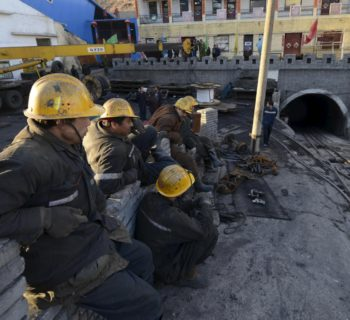 Rescuers sit next to the entrance of a coal mine after a flooding incident in Datong, Shanxi province April 20, 2015. Seven miners were found dead and 17 others remained trapped inside a flooded coal mine in north China's Shanxi Province, Xinhua News Agency reported. Picture taken April 20, 2015. REUTERS/Stringer CHINA OUT. NO COMMERCIAL OR EDITORIAL SALES IN CHINA
