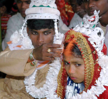 An Indian groom puts vermilion, the holy mark belived the as sign of hindu marriage, on the forehead of his underage bride during a mass marriage programme in the village of Malda, some 360 Kms. northeast of Kolkata, 02 March 2006.  India amended its Child Marriage Restraint Act in 1978, setting 18 as the minimum age for a woman to marry and 21 for a man, and lawmakers hoped in vain that the threat of fines and imprisonment would curb under-age marriages, but the practice continues.  / AFP PHOTO / STRDEL