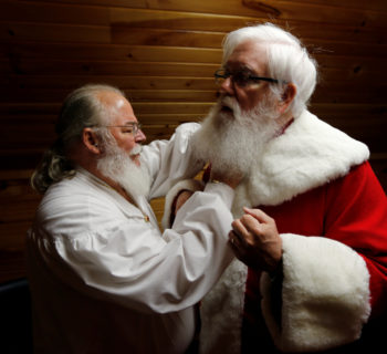 Santa Jim Hastings (R) from Durham, North Carolina, is helped into his suit by a fellow Santa prior to a visit from a group of children at the Santa House in Midland, Michigan, U.S. October 28, 2016. REUTERS/Christinne Muschi