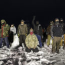 Military veterans stand on a closed bridge to protest across from police protecting the Dakota Access oil pipeline site in Cannon Ball, N.D., Thursday, Dec. 1, 2016. Some military veterans in North Dakota disagree with the 2,000 veterans planning to join a protest opposing the four-state, $3.8 billion Dakota Access pipeline. (AP Photo/David Goldman)