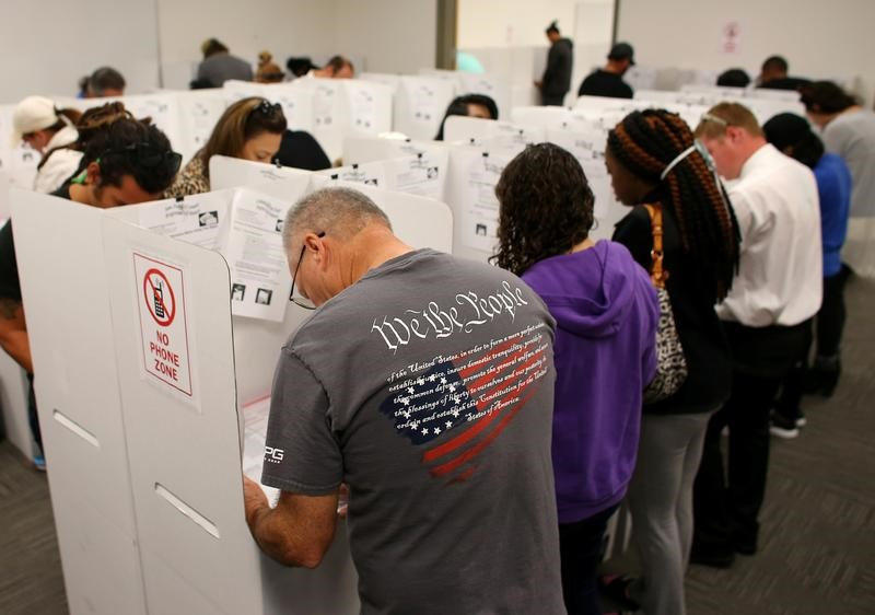 A voter wears a shirt with words from the United States Constitution while casting his ballot early as long lines of voters vote at the San Diego County Elections Office in San Diego, California, U.S., November 7, 2016.       REUTERS/Mike Blake