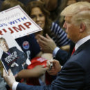 FILE - In this May 6, 2016 file photo, Republican presidential candidate Donald Trump looks at his photo on a magazine cover as he signs autographs during a rally in Eugene, Ore. The city of Eugene plans to bill the Donald Trump campaign nearly $100,000 to pay for costs associated with last month's visit. Police Chief Pete Kerns said in an email Wednesday, June 22, 2016, that overtime compensation for police officers totaled $78,000 while firefighters and other city employees racked up another $10,000 in OT. (AP Photo/Ted S. Warren, file)