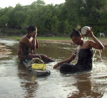 In this photo taken Sunday, May 30, 2010, Myanmar women bath in a creek  in a village near Myanmar's new administrative city Nay Pyi Taw, Myanmar. Rain in early monsoon filled water in dried-up creeks as the monsoon has already arrived in the country.(AP Photo/Khin Maung Win)