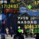 People are reflected in a display showing the Nikkei average (top in L) and the NASDAQ average of the U.S outside a brokerage in Tokyo, Japan, November 7, 2016. REUTERS/Kim Kyung-Hoon