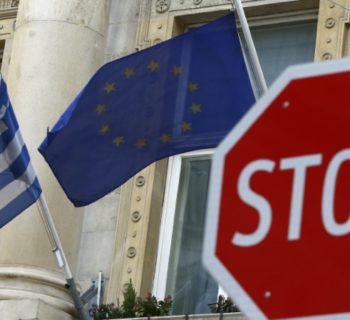 The Greek (L) and European Union flags are seen behind a stop sign in front of the Greek embassy in Vienna, Austria, February 25, 2016.   REUTERS/Leonhard Foeger