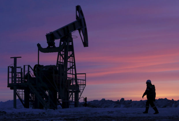 A worker walks past a pump jack on an oil field owned by Bashneft in Bashkortostan, Russia, January 28, 2015.      REUTERS/Sergei Karpukhin/File Photo