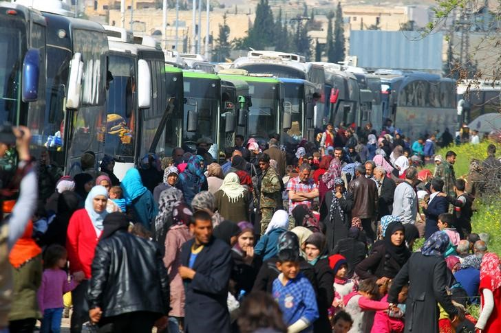 FILE PHOTO: People that evacuated from the two villages of Kefraya and al-Foua walk near buses, after a stall in an agreement between rebels and Syria's army, at insurgent-held al-Rashideen, Aleppo province, Syria April 15, 2017. REUTERS/Ammar Abdullah/File photo